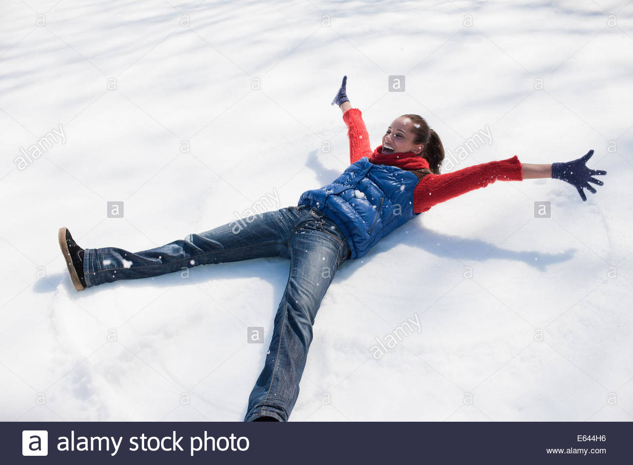 Enthusiastic woman making snow angel - Stock Image