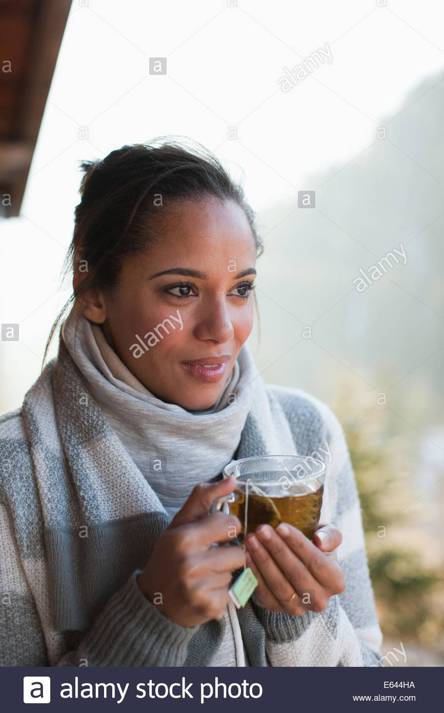 Portrait of smiling woman drinking tea - Stock Image