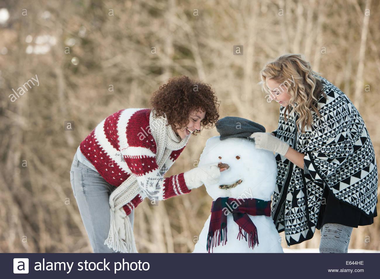 Two women building snowman - Stock Image