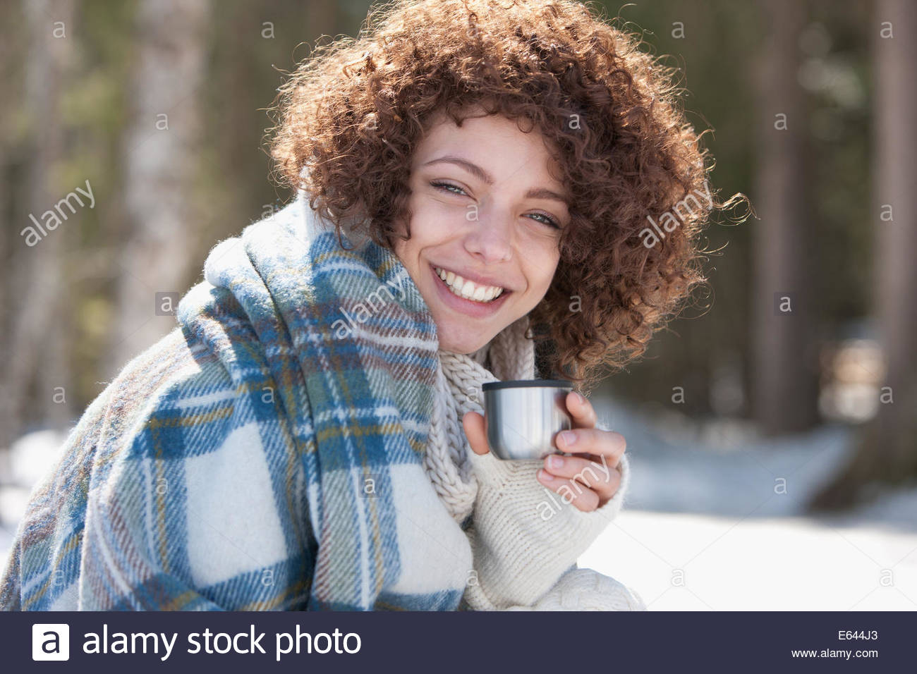 Woman drinking warm beverage outdoors, winter - Stock Image