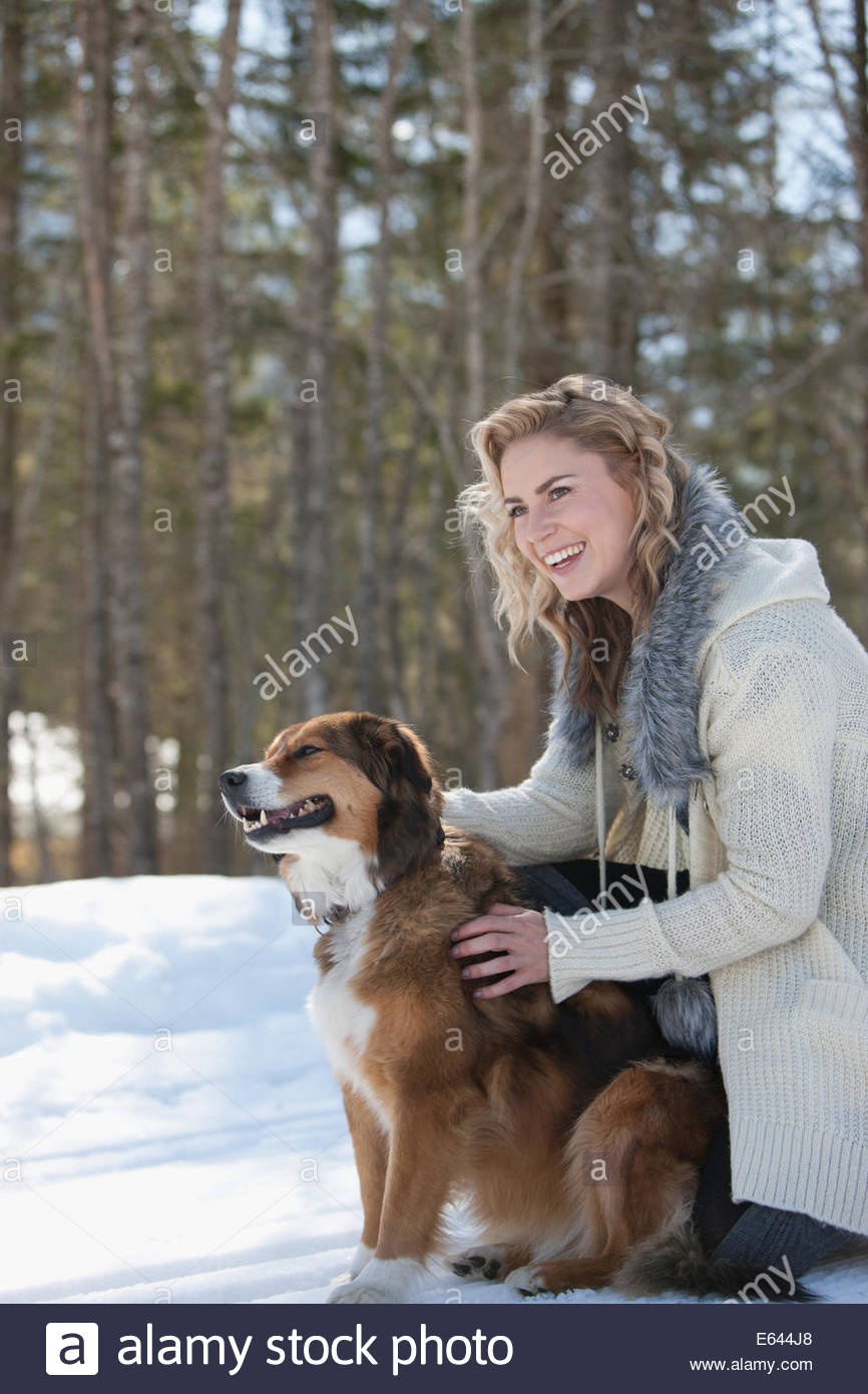 Woman and dog outdoors in snow - Stock Image