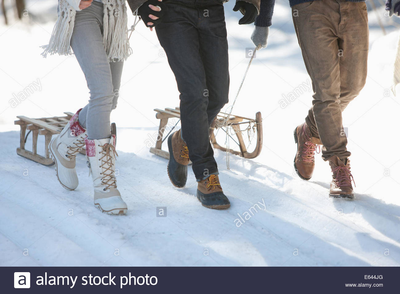 Three people with sled in snowy landscape, low section - Stock Image
