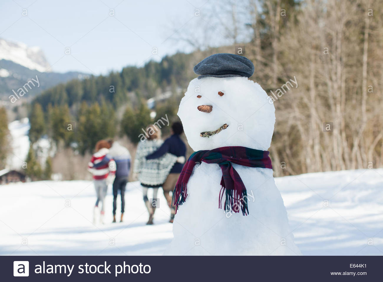 Snowman, people walking in background - Stock Image