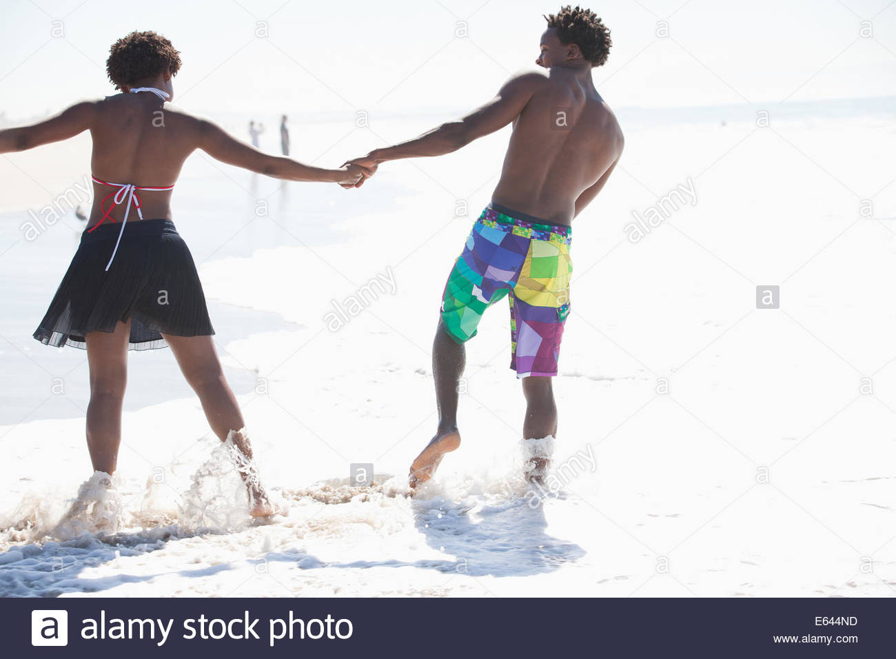 Couple walking in waves on beach Stock Photo