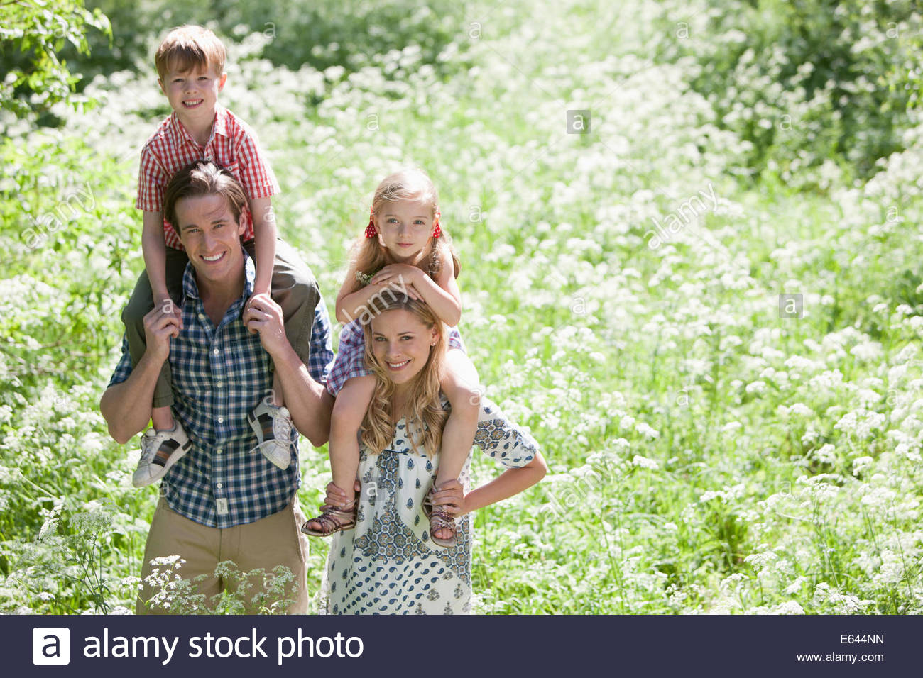 Parents holding children on shoulders in park - Stock Image