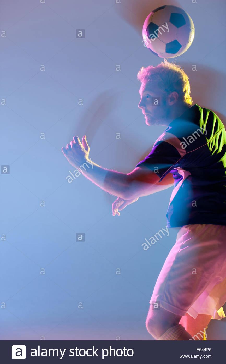 Athlete heading soccer ball - Stock Image