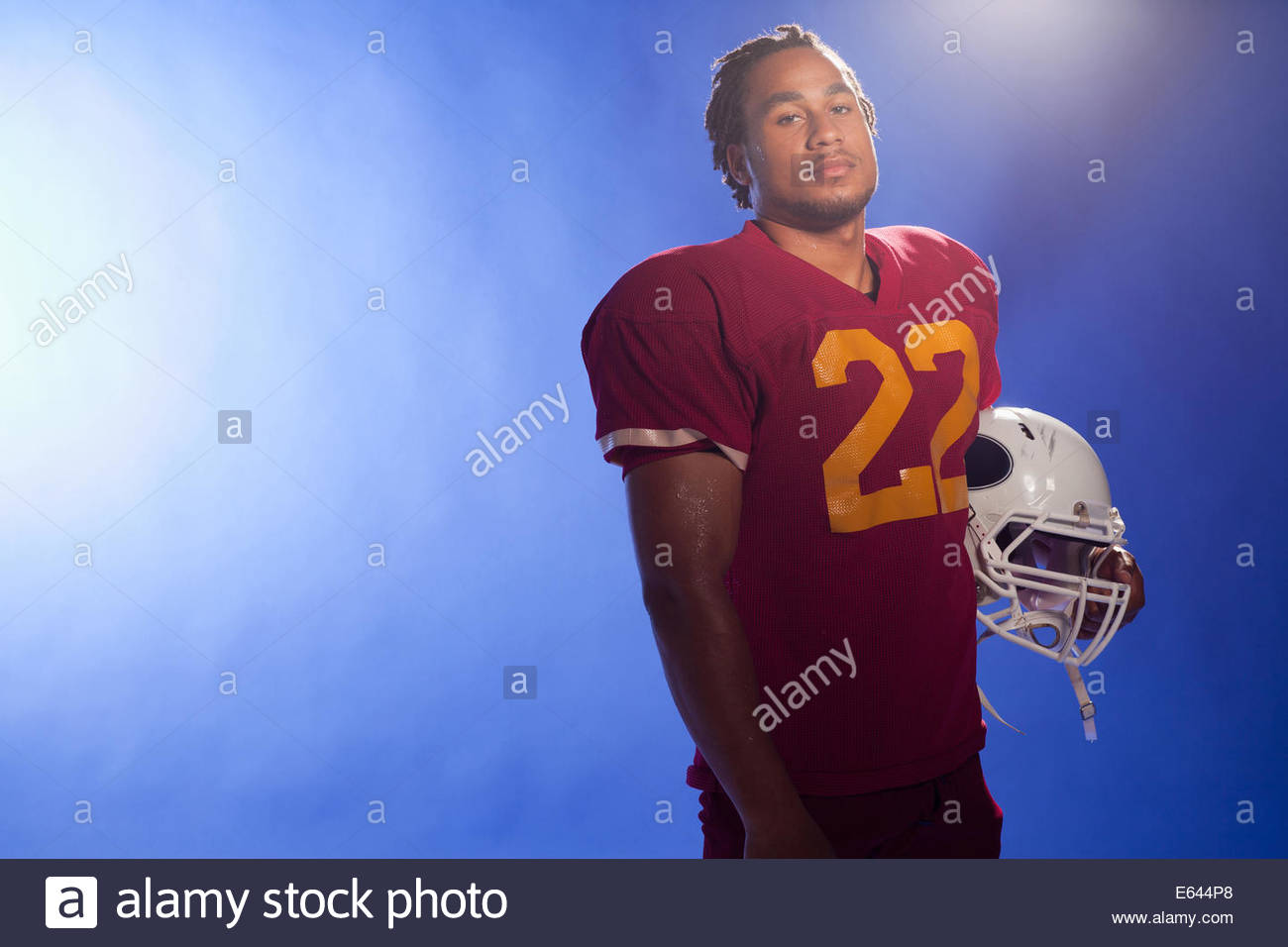 Football player carrying helmet - Stock Image