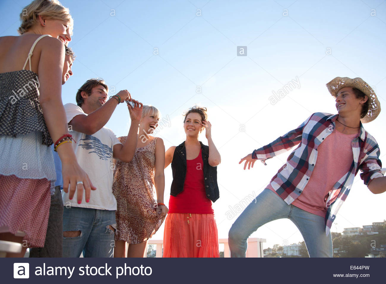 Man with digital camera taking photograph of friends - Stock Image