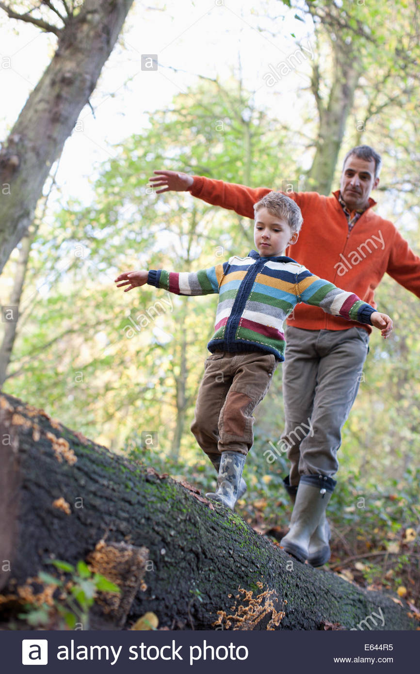 Father helping son cross log outdoors - Stock Image
