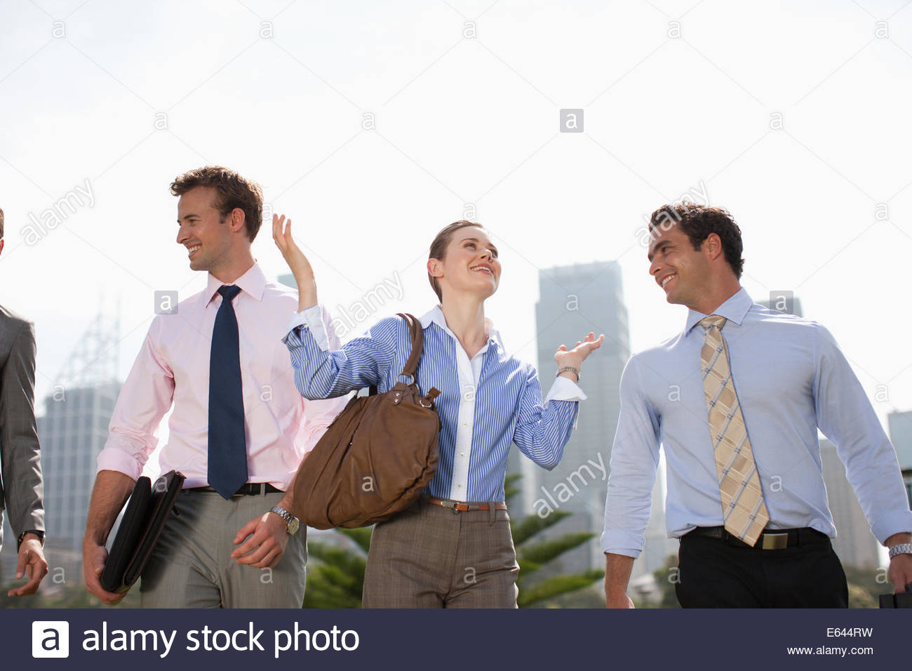 Business people walking together outdoors - Stock Image