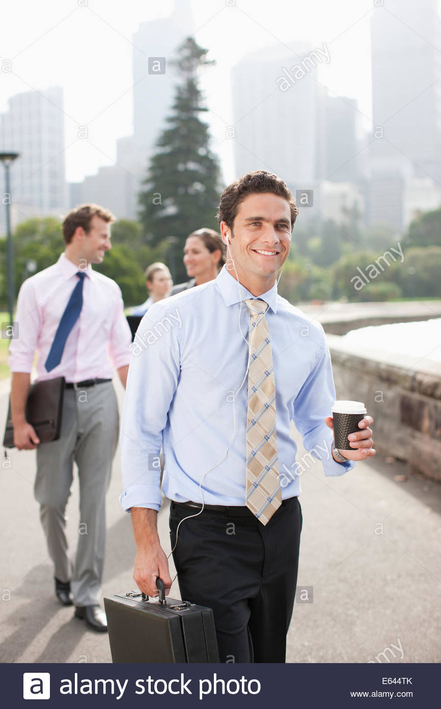 Businessman listening to headphones and carrying coffee - Stock Image