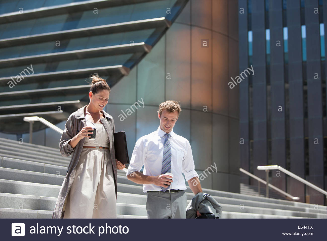 Business people walking down steps outdoors Stock Photo