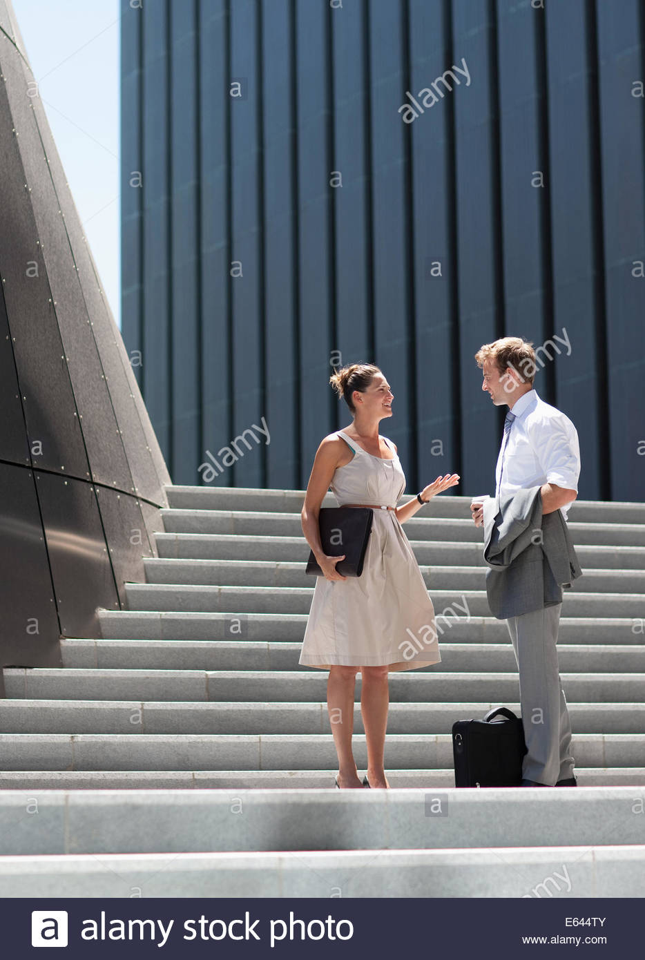 Business people talking on steps outdoors - Stock Image