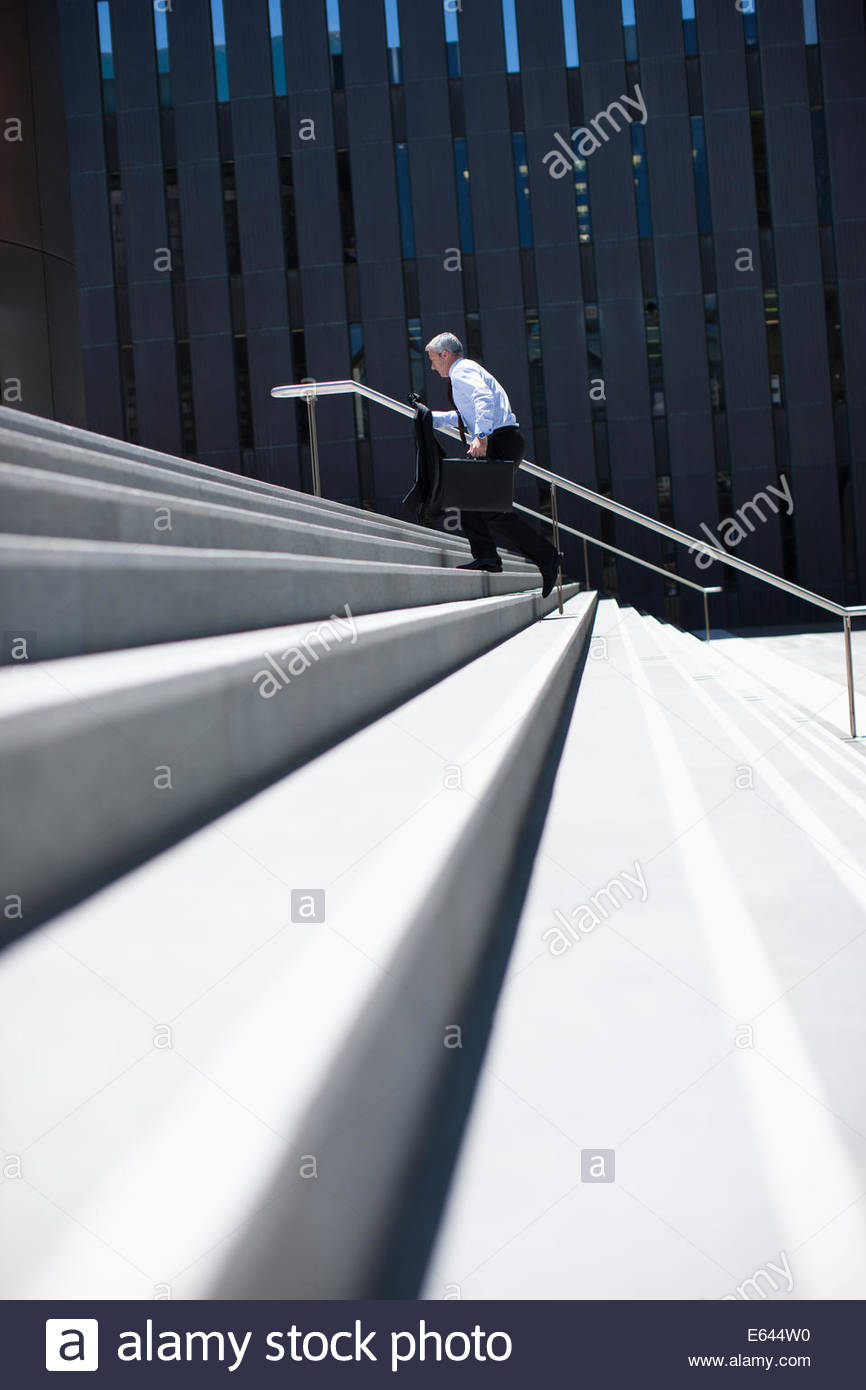 Businessman rushing up steps outdoors - Stock Image