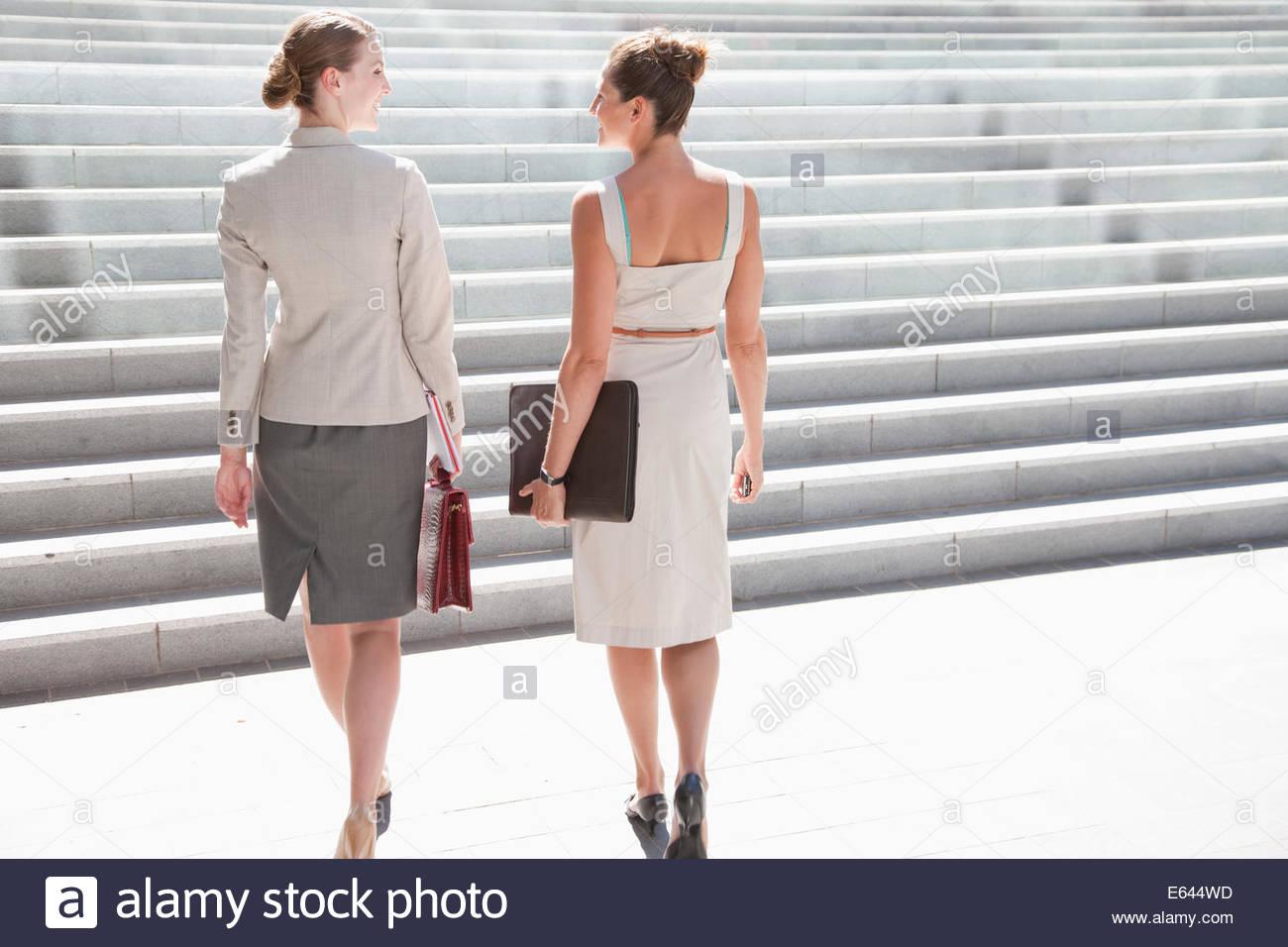 Businesswomen walking up steps outdoors - Stock Image