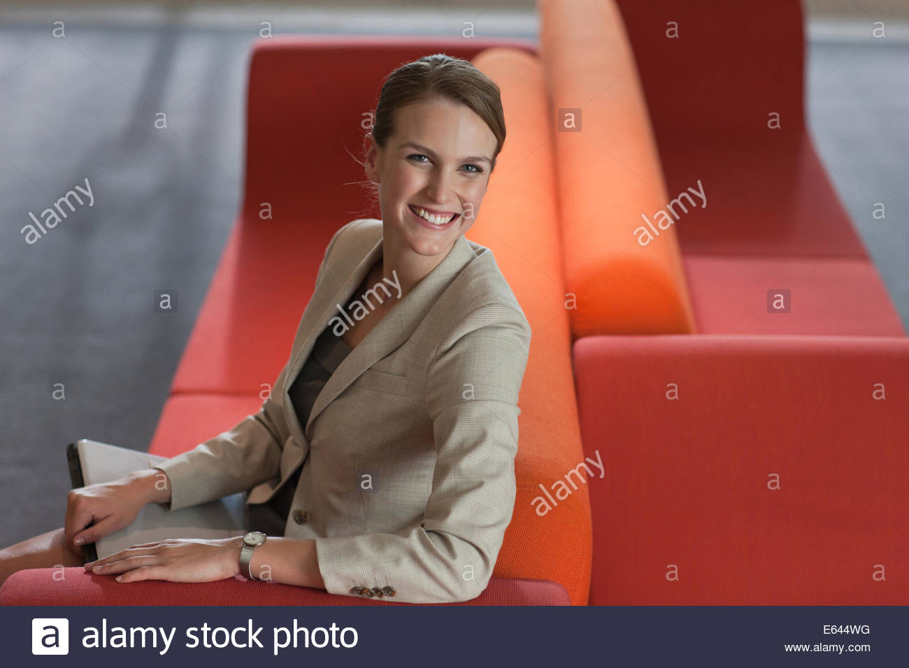 Businesswoman with laptop in waiting area - Stock Image