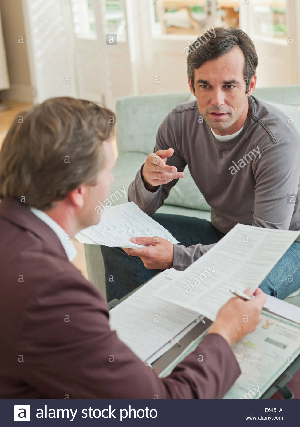 Man meeting with financial advisor in living room - Stock Image