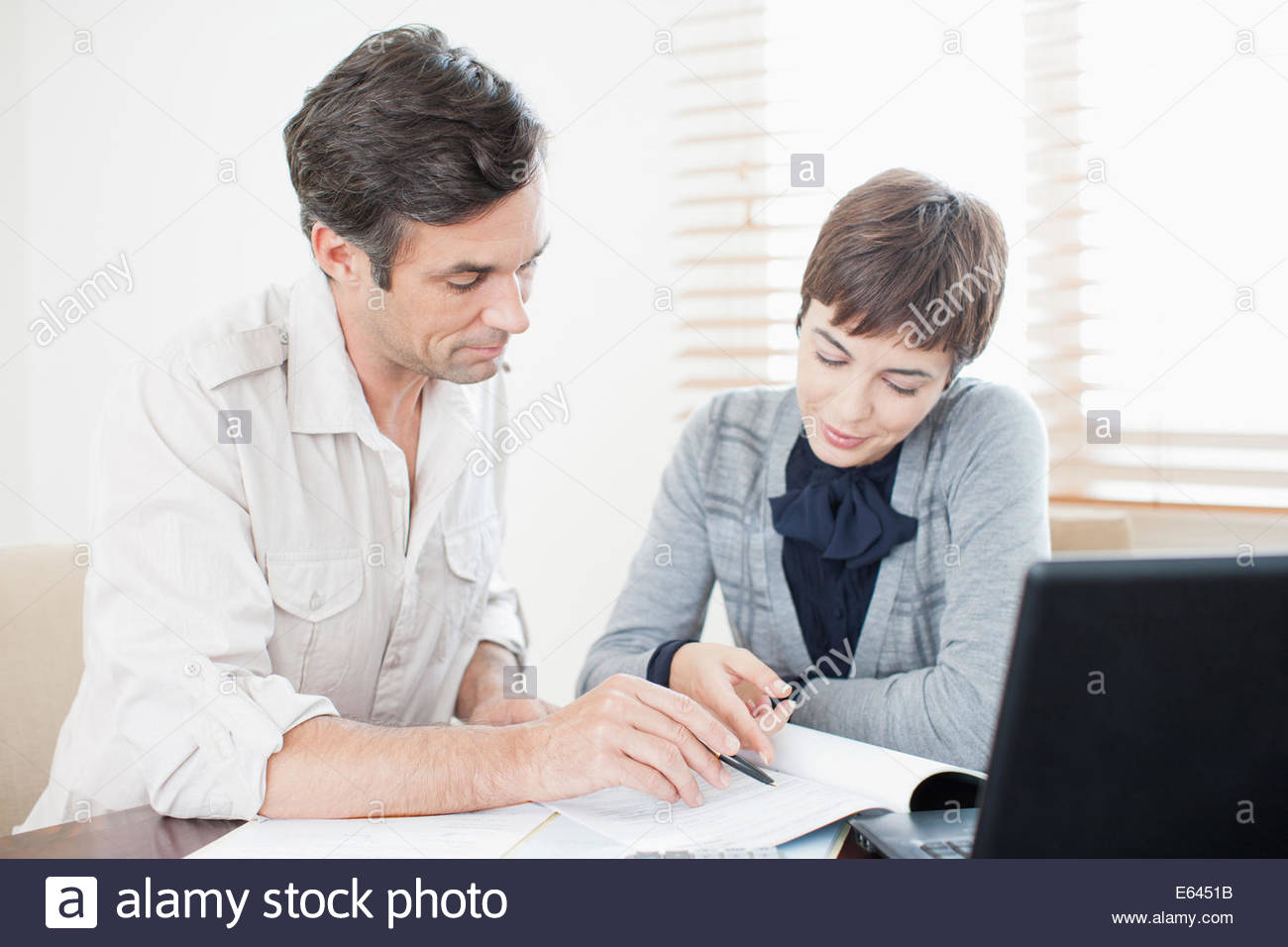 Businesswoman guiding man with paperwork Stock Photo