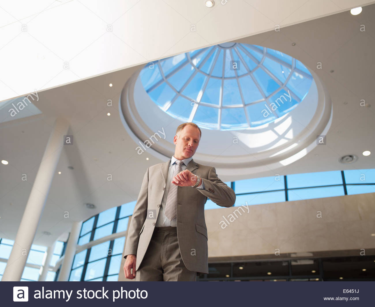 Businessman checking wristwatch - Stock Image