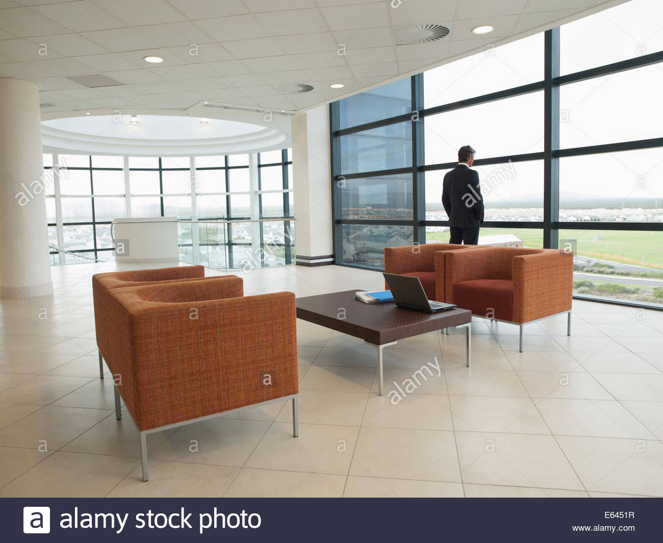 Businessman standing in modern waiting area - Stock Image