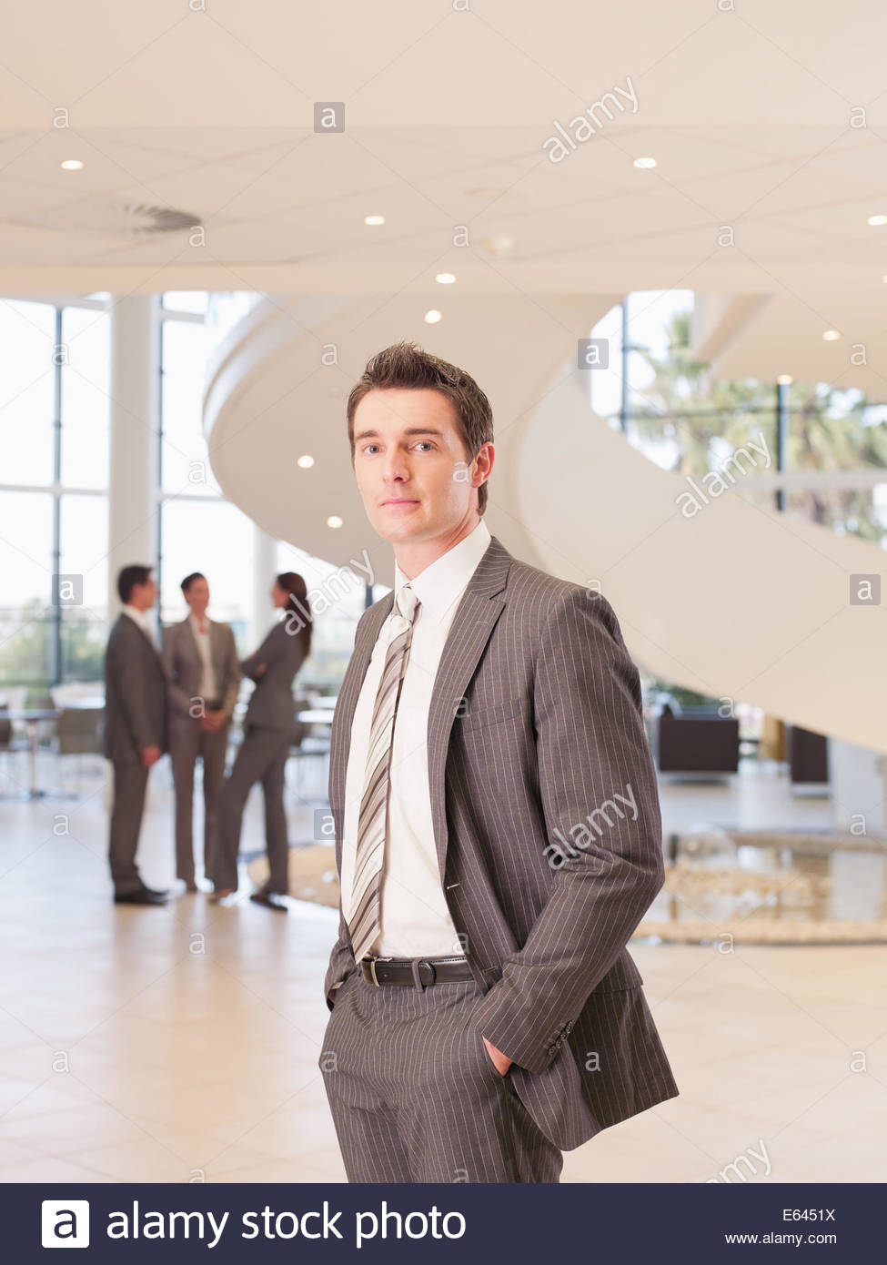 Businessman standing in office lobby - Stock Image