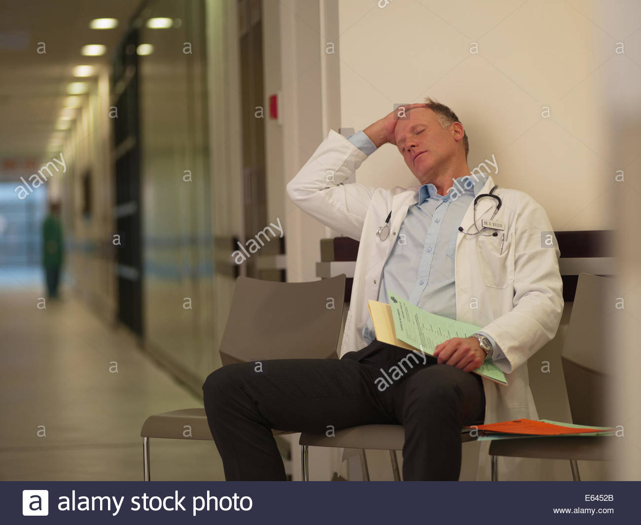 Tired doctor sitting in hospital waiting area - Stock Image