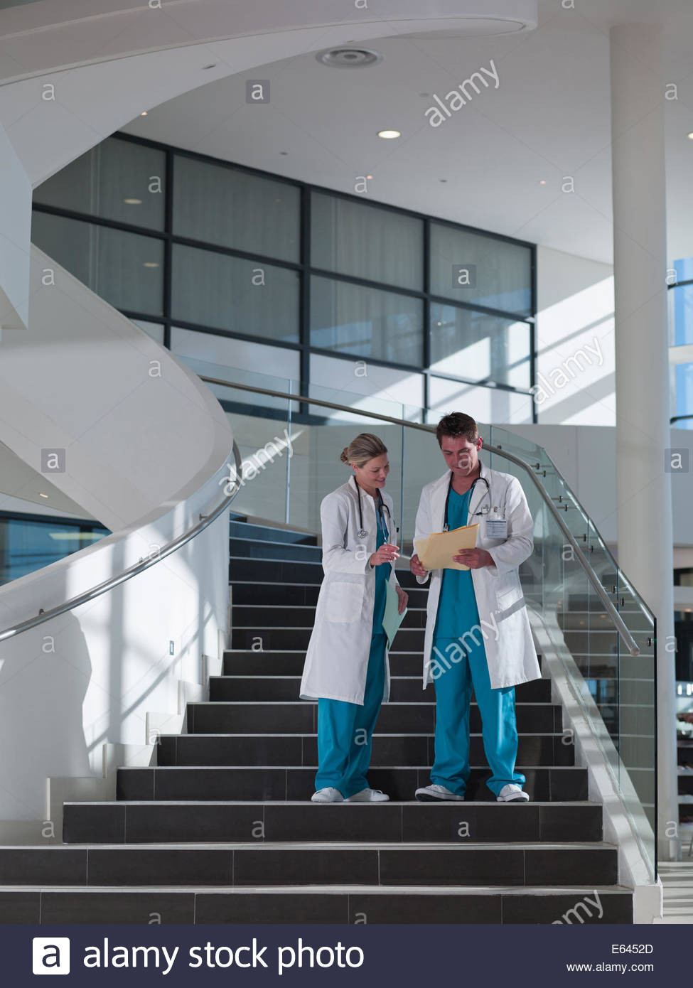 Doctors walking down staircase in hospital - Stock Image