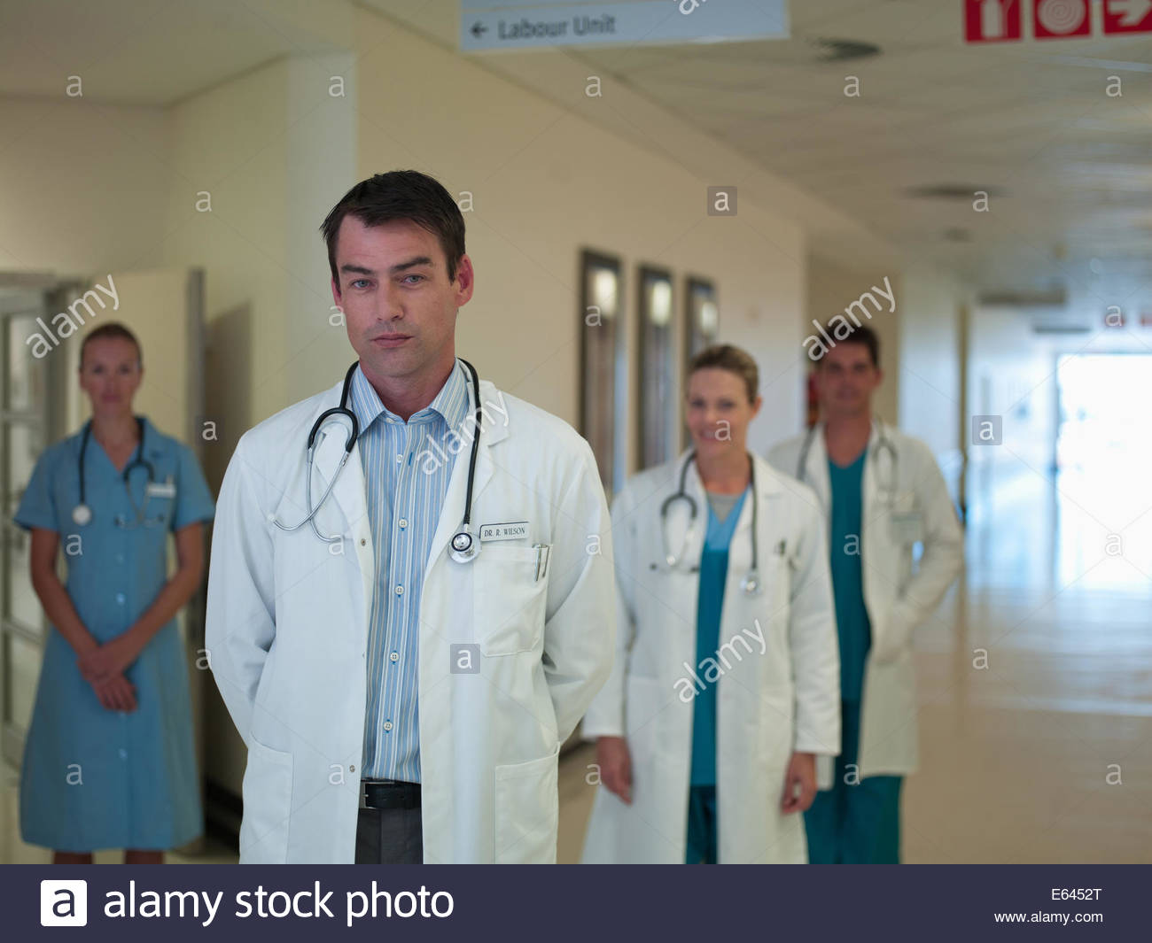 Doctors and nurse standing in hospital corridor - Stock Image