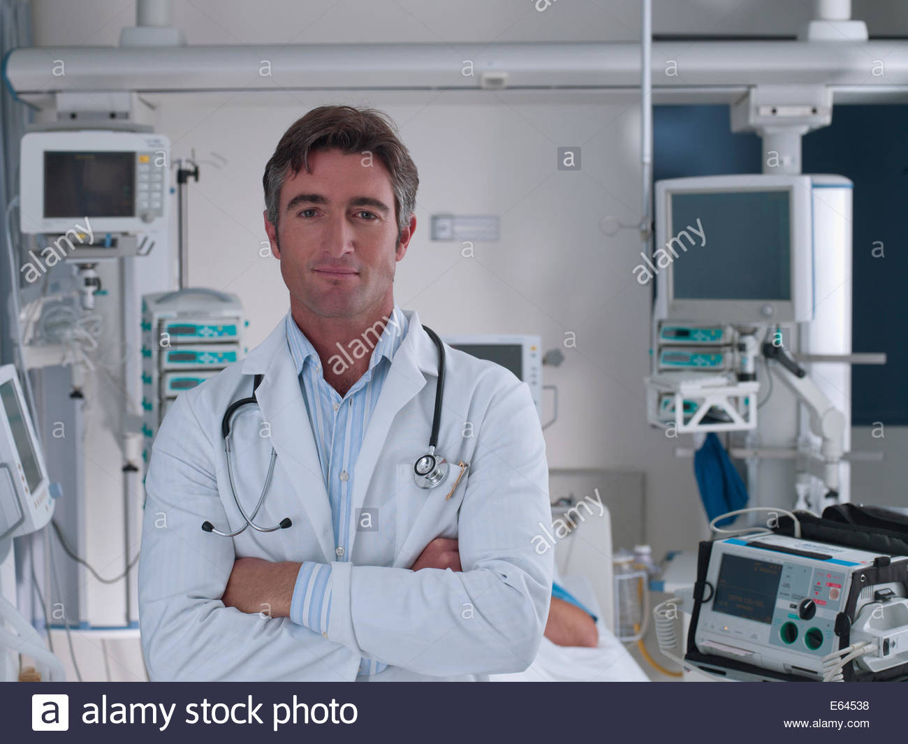 Doctor standing in hospital intensive care with arm closed - Stock Image