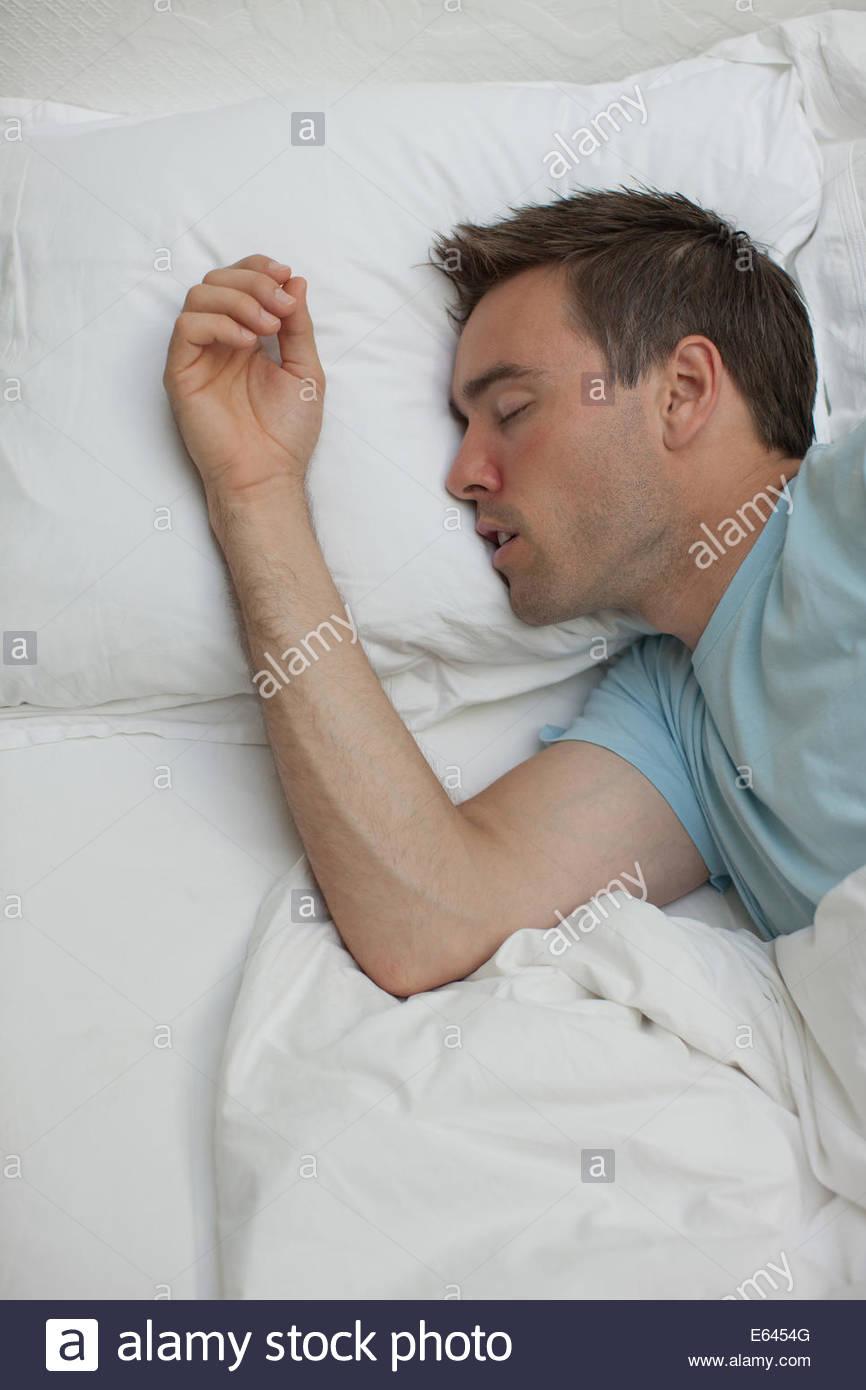 Sick man sleeping in bed - Stock Image