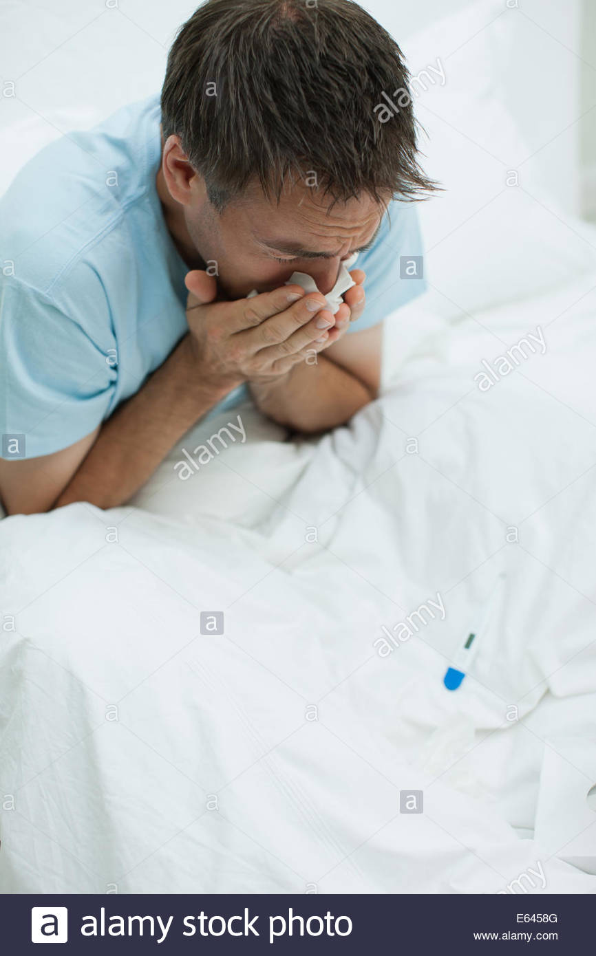 Sick man in bed blowing nose - Stock Image