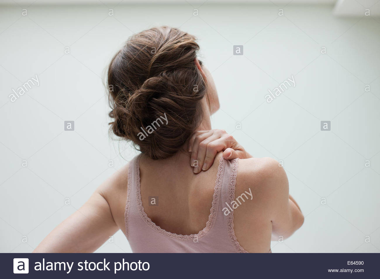 Woman rubbing aching back - Stock Image