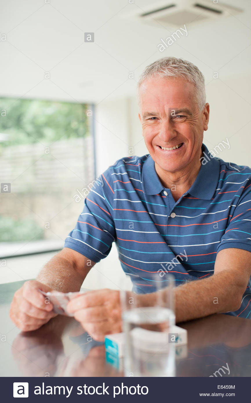 Happy man holding with glass at table - Stock Image