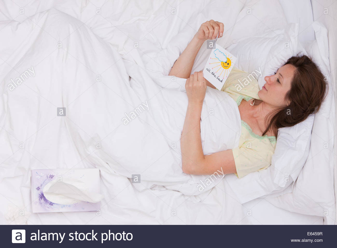 Sick woman laying bed reading get well card - Stock Image