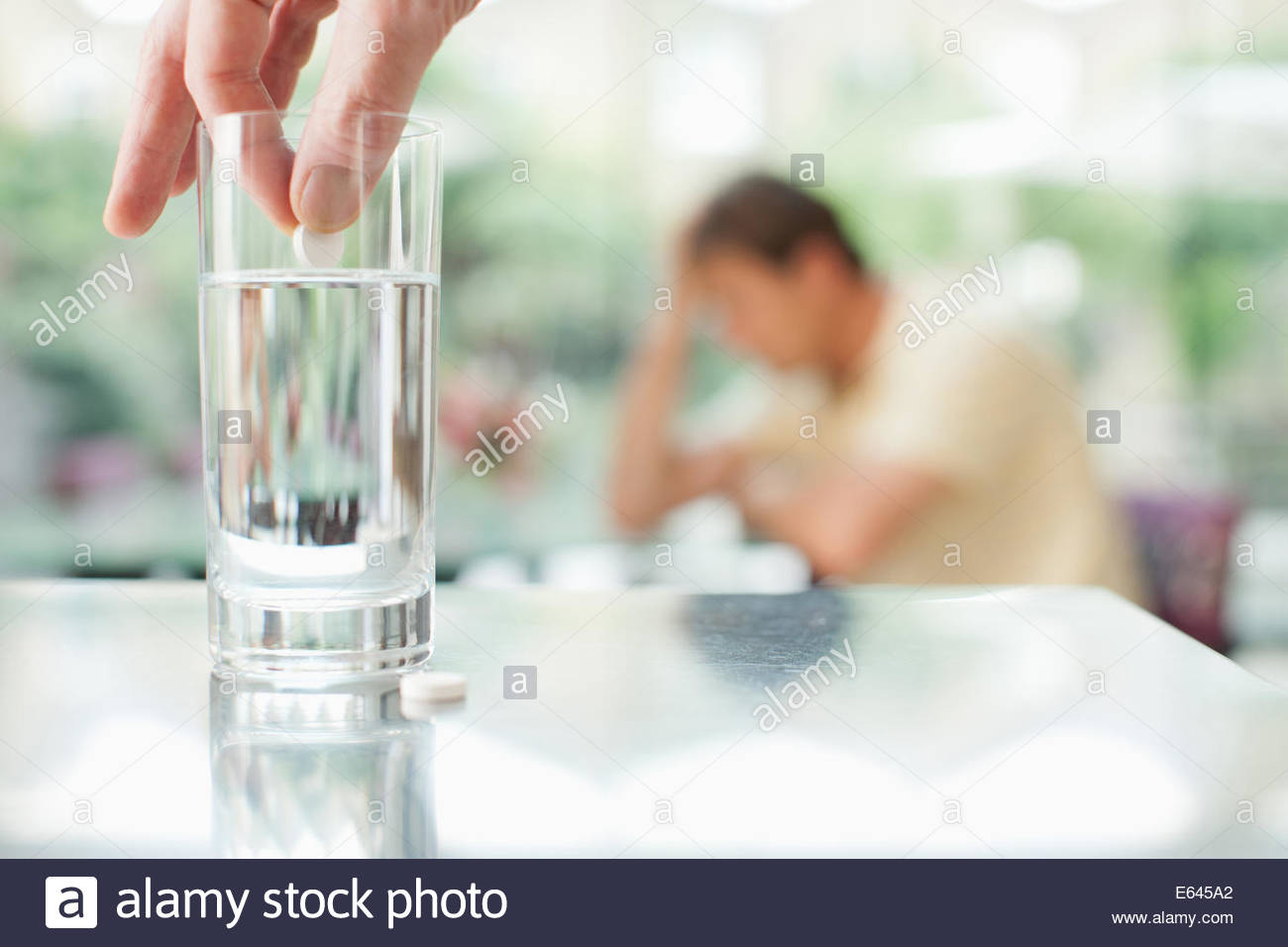 Putting pill in glass of water with unhappy man in background - Stock Image