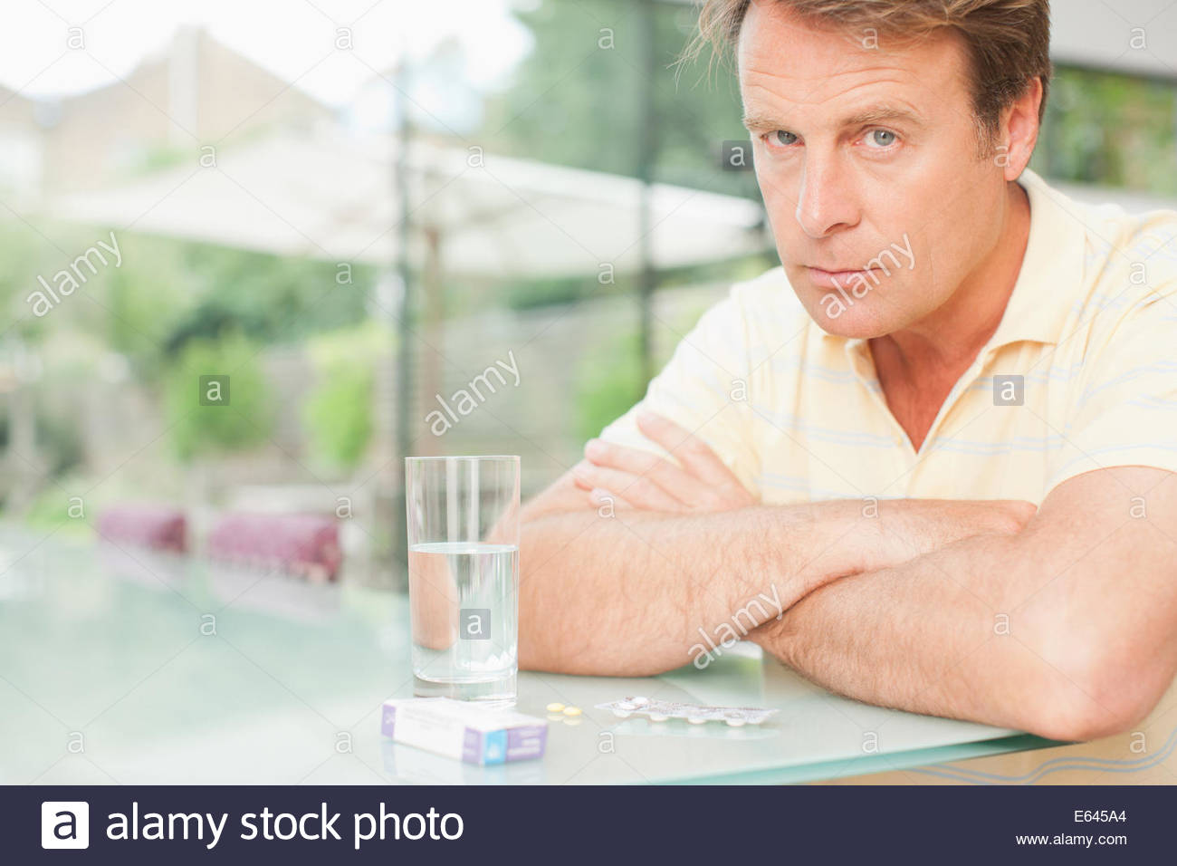 Man sitting with glass of water and box of pills - Stock Image