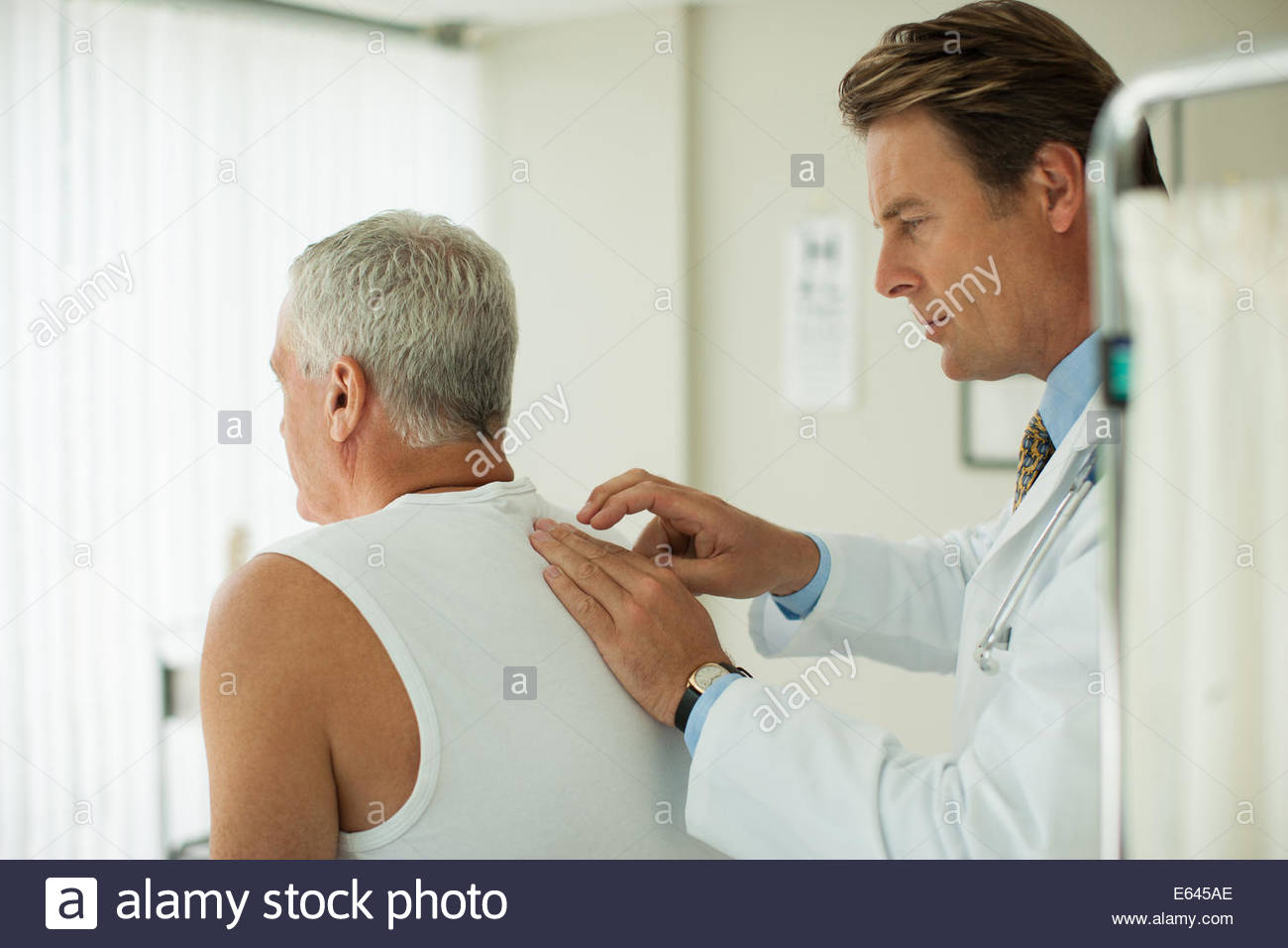 Doctor tapping on patientÂ's back - Stock Image
