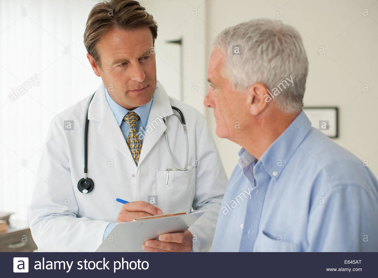 Doctor talking with patient in doctorÂ's office - Stock Image