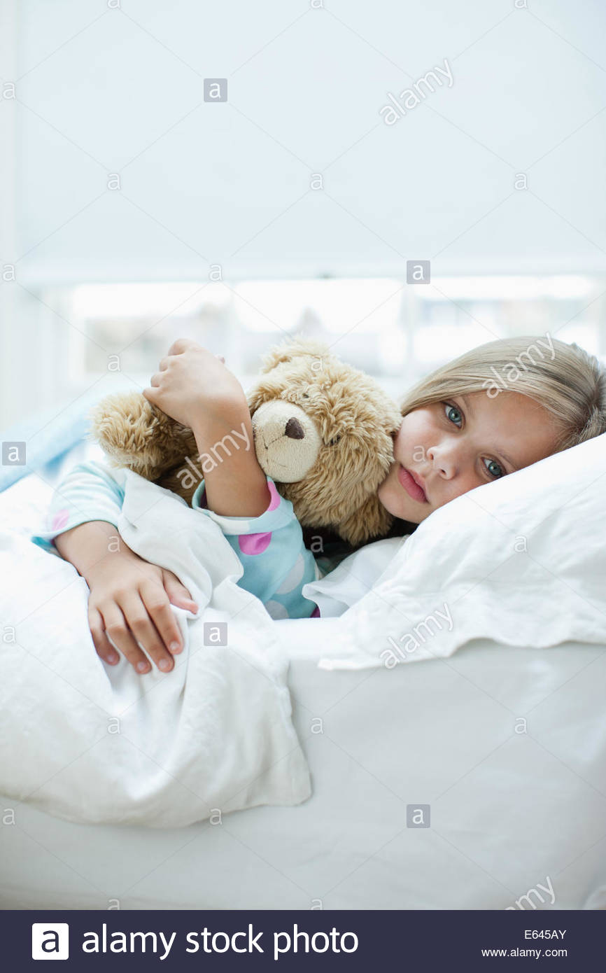 Sick girl laying in bed with teddy bear - Stock Image