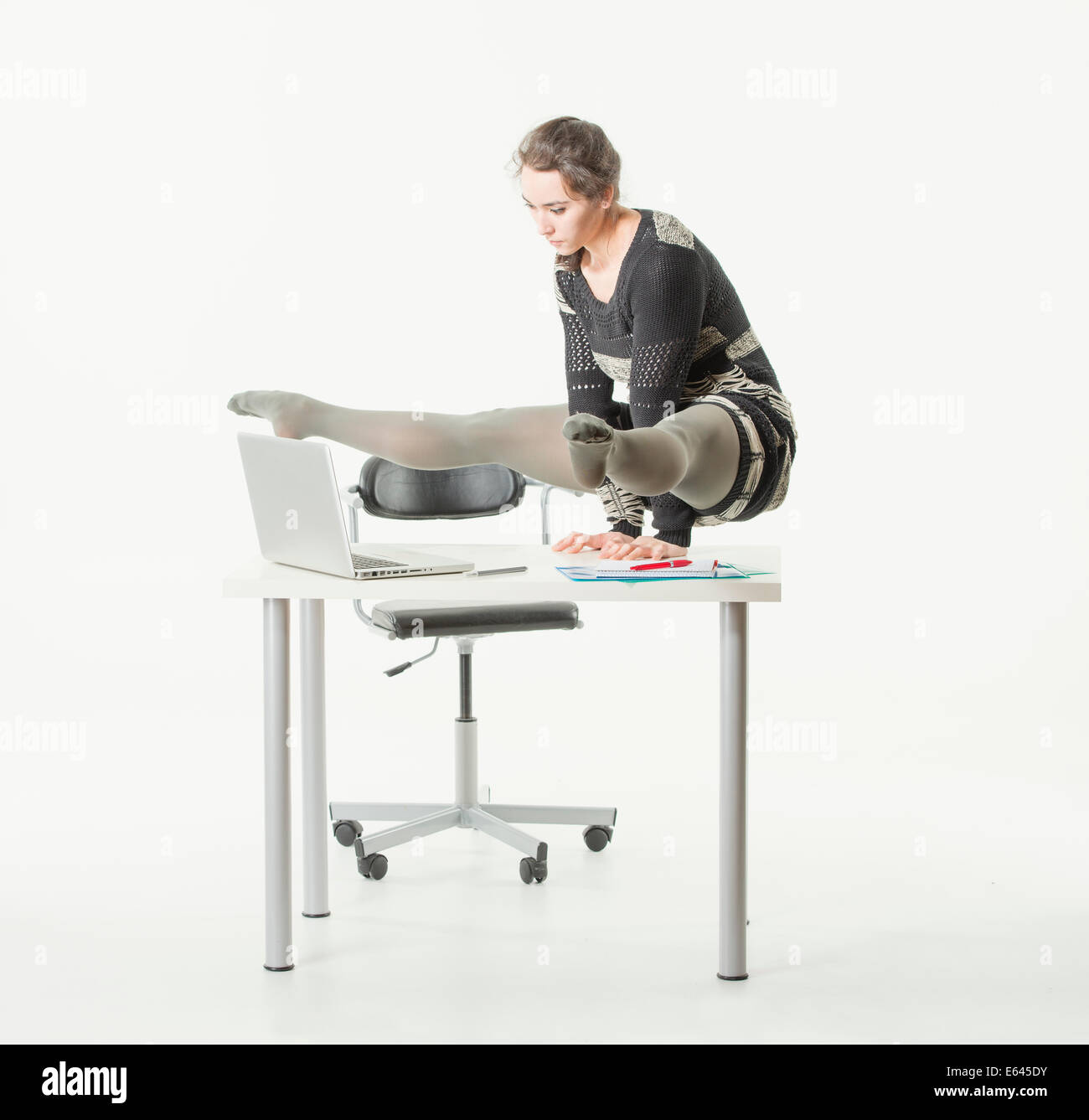 Young woman balancing on her hands on an office desk while looking at her computer Stock Photo