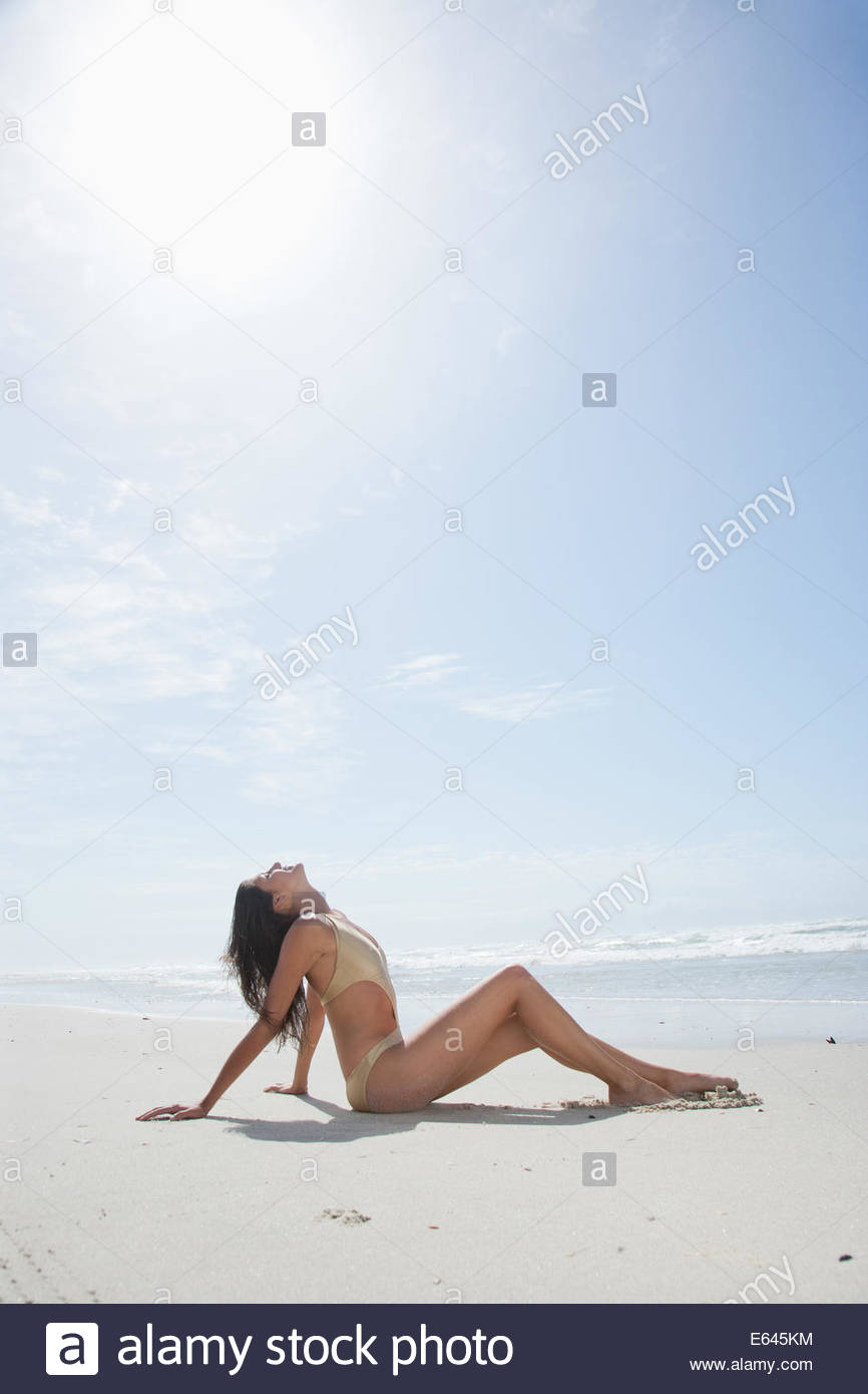 Woman in bathing suit sunbathing on beach Stock Photo