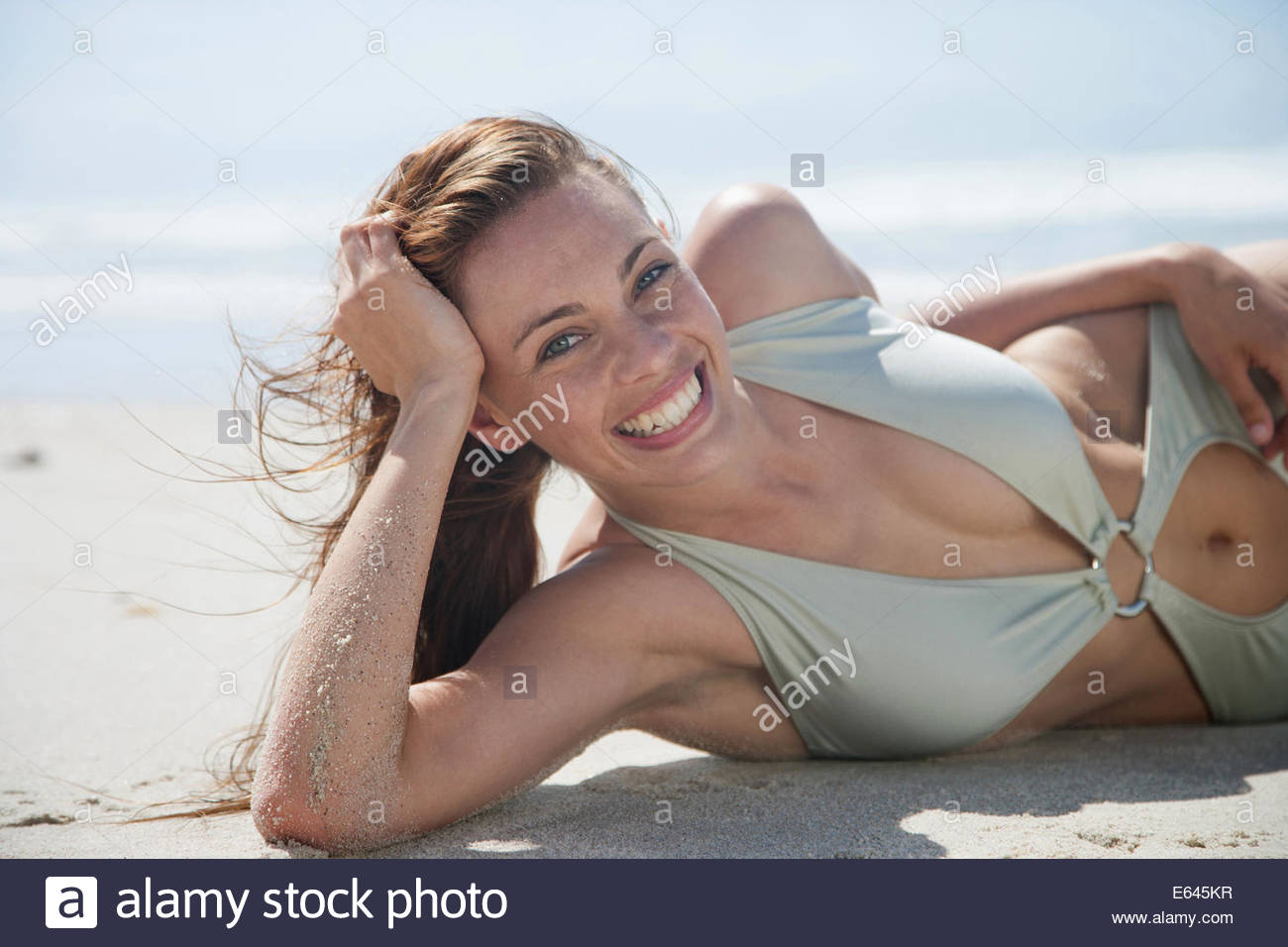 Woman in bathing suit laying on beach - Stock Image