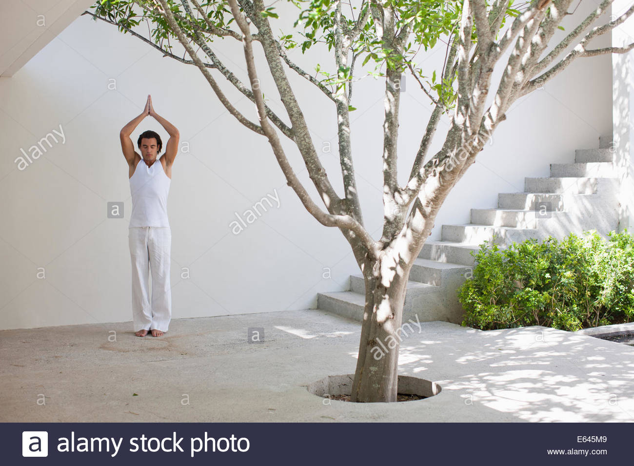 Man standing with arms outstretched in courtyard - Stock Image