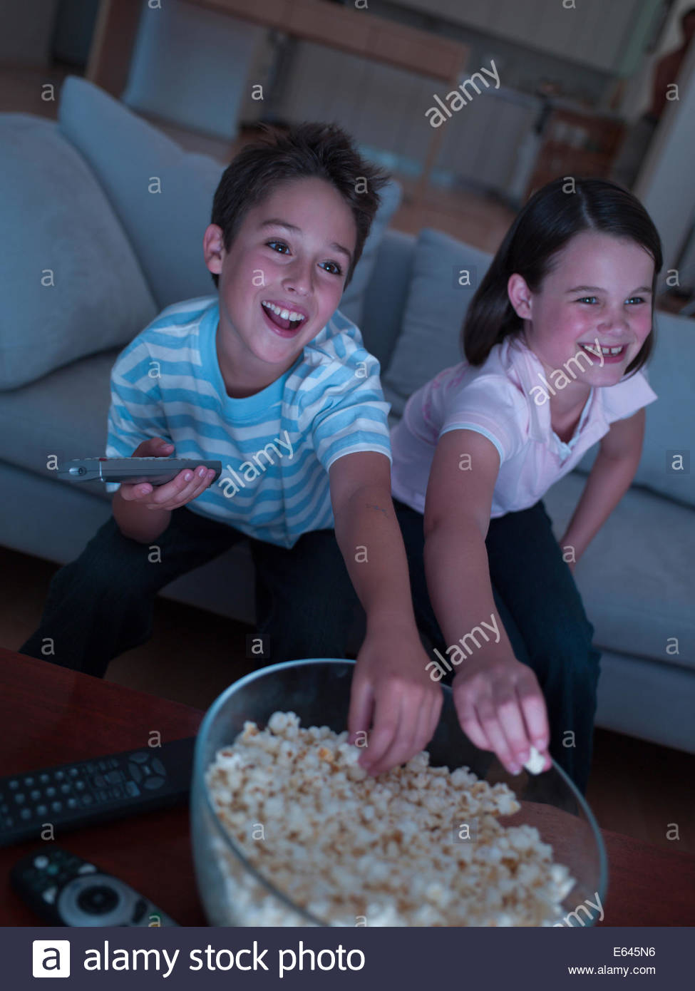 Boy and girl eating popcorn and watching TV - Stock Image