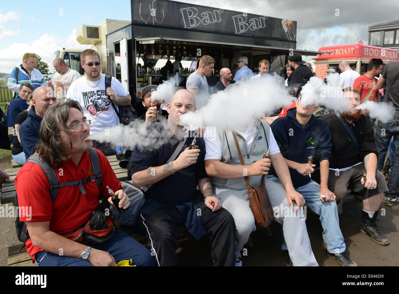 Men exhaling vapour from electronic e cigarette at Vapefest 2014 - Stock Image