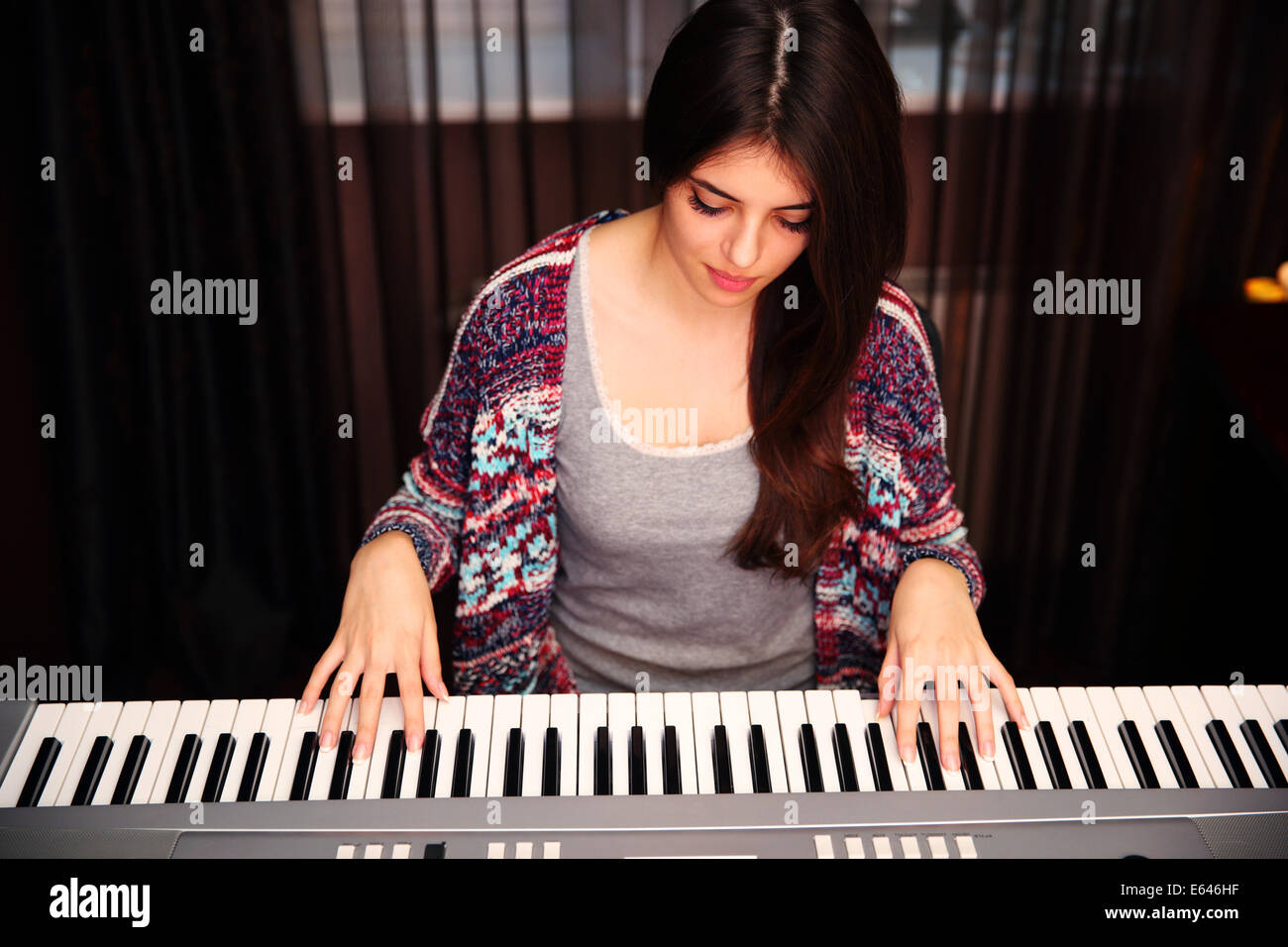 Young beautiful woman playing on piano at home - Stock Image