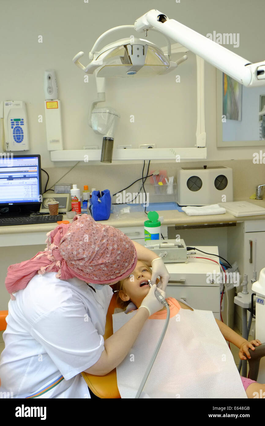 Young girl has her teeth cleaned by a dental hygienist at the dentist - Stock Image