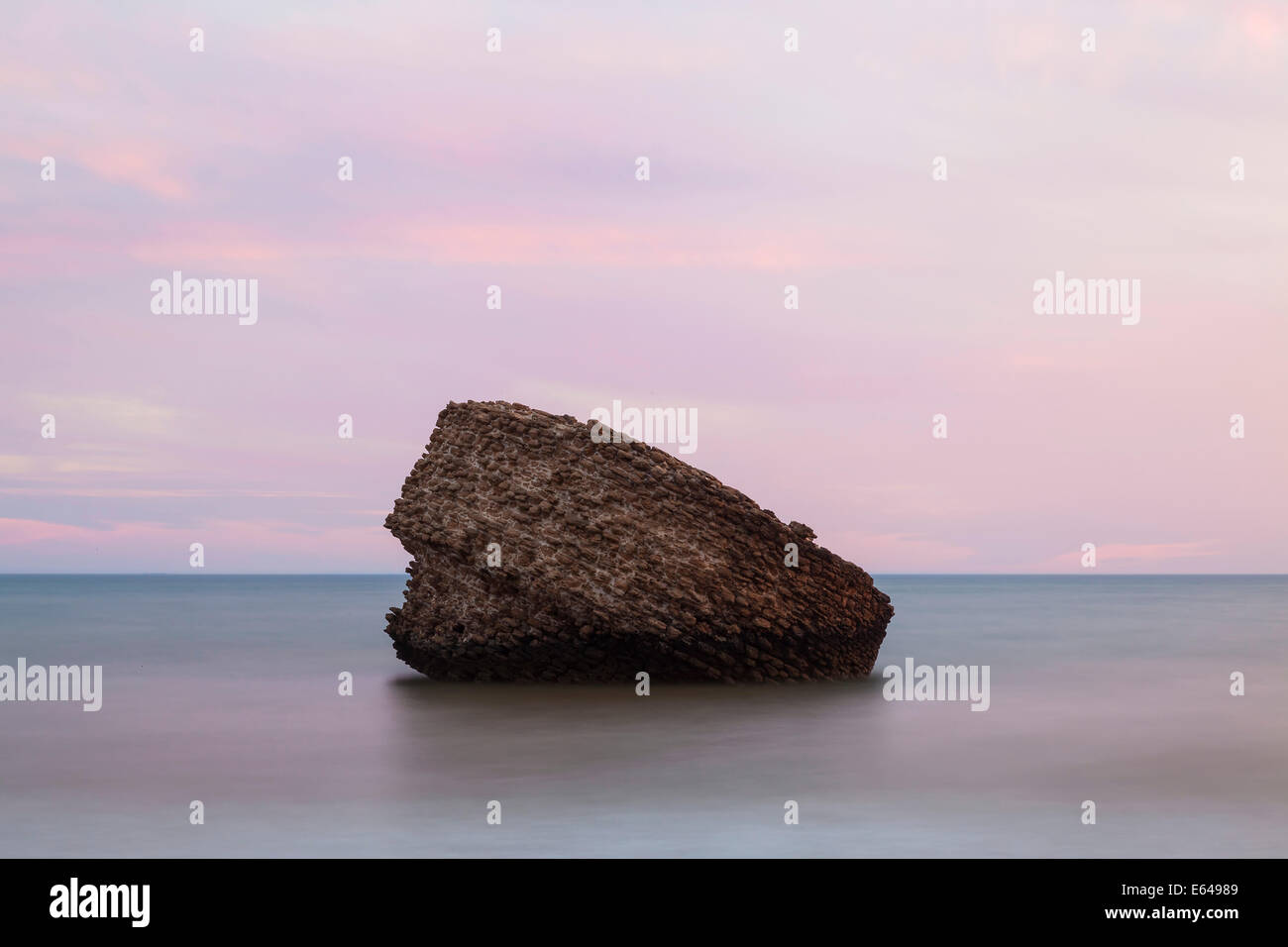 Rock (an old watch tower or beacon) at Matalascañas beach at sunset, Andalucia, Spain Stock Photo