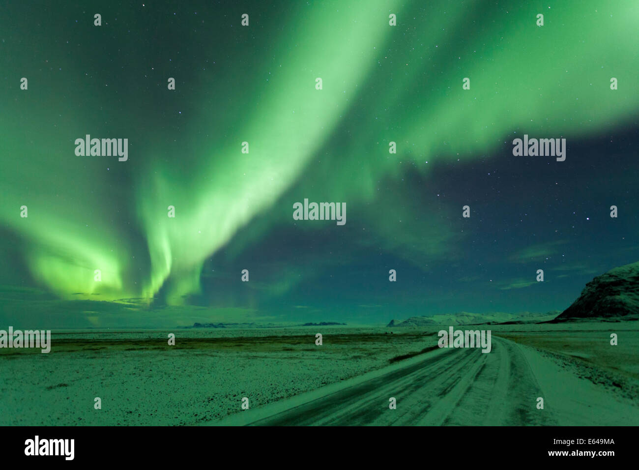Northern Lights, Aurora Borealis, Winter road with snow, Iceland - Stock Image