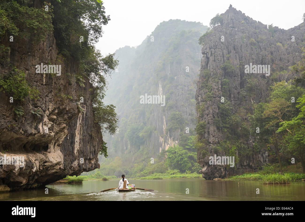Woman rowing along Ngo Dong River, Tam Coc nr Ninh Binh, nr Hanoi, Vietnam - Stock Image